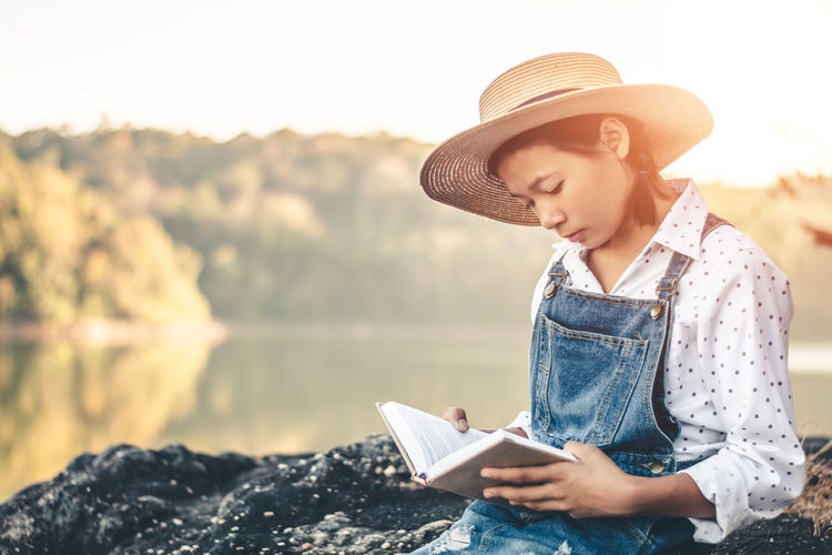 Lifestyles Women Nature Outdoors Holding Education Book Real People One Person Reading Beauty In Nature Water Hat Reading A Book