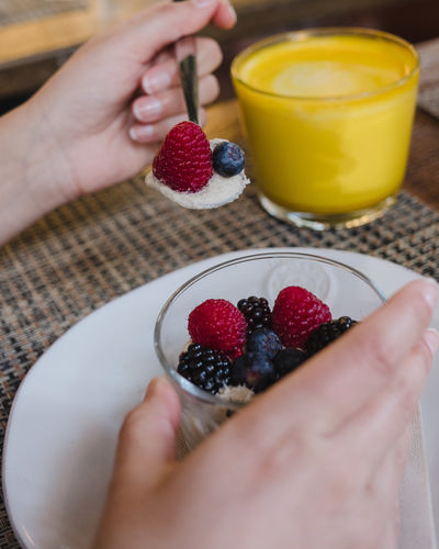 Food And Drink Healthy Eating Berry Fruit Human Hand Fruit Food Freshness One Person Hand Human Body Part Wellbeing Real People Holding Table Drink Strawberry Raspberry Indoors  Lifestyles Meal Breakfast Finger Glass Temptation