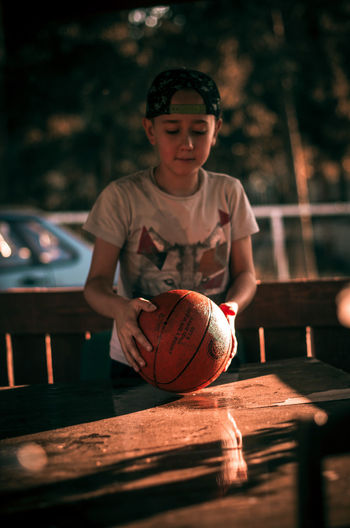 Boy holding ball on table