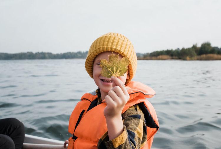 Portrait of boy holding hat against lake