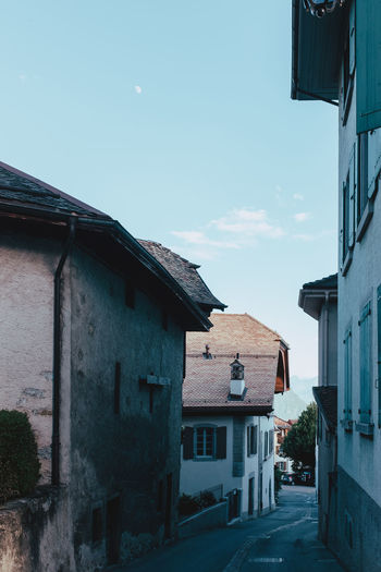 Houses by street in town against sky