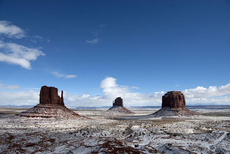 Scenic View Of Snow Covered Monument Valley Against Blue Sky