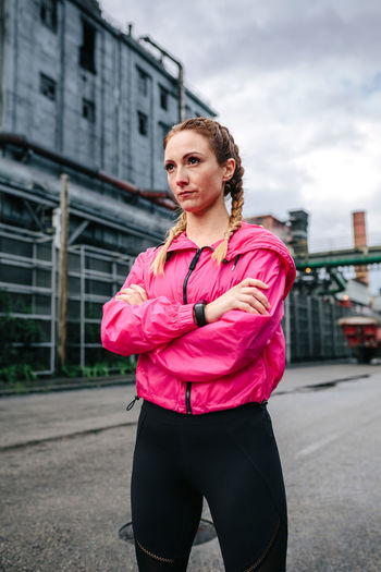 Portrait of beautiful woman standing against city in background