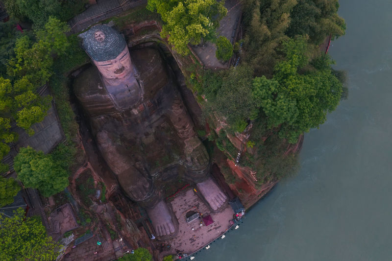 Leshan Giant Buddha China Sichuan Leshan Giant Buddha Buddha Buddha Statue Statue Art River Water Travel Travel Destinations Architecture Mountain Rock - Object Tree History Nature Beauty In Nature Sculpture Outdoors Plant Day Tranquility Aerial View