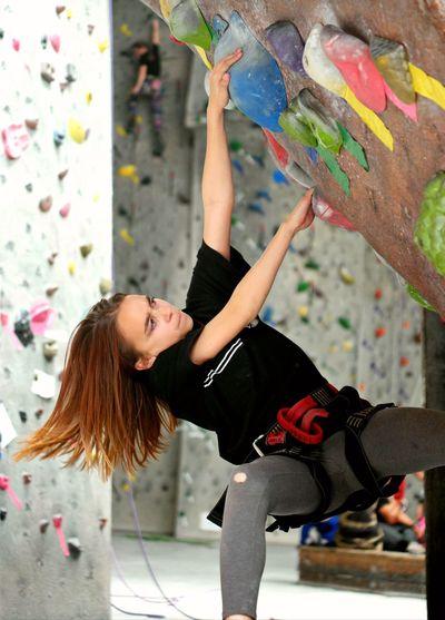 Focused girl climbing on wall