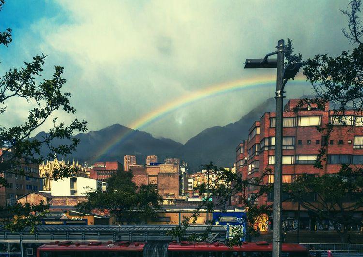 Rainbow over buildings against cloudy sky