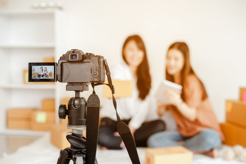 Close-up of camera photographing female coworkers in home office