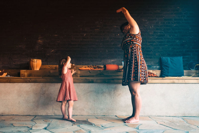 Side view full length of woman standing with daughter