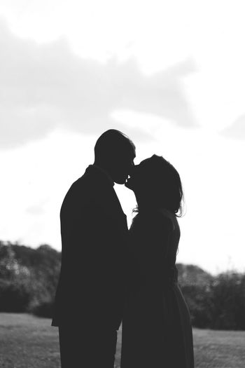 Silhouette couple standing against sky