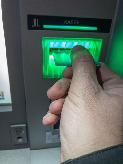 Entering the bank card at an ATM at dusk that is lighted green - Moneybox Atm Cash Box Input Enter Bank Card Ec Card Maestro Card Security Secure Human Finger Human Hand Money Cash Switzerland Swiss Franc CHF Finance Taking Off Withdraw Money Obtain Receive Economy Bank