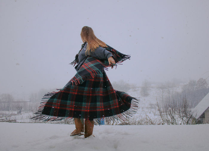 Woman dancing on snow covered land