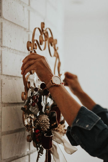 Close-up of man holding hanging against wall