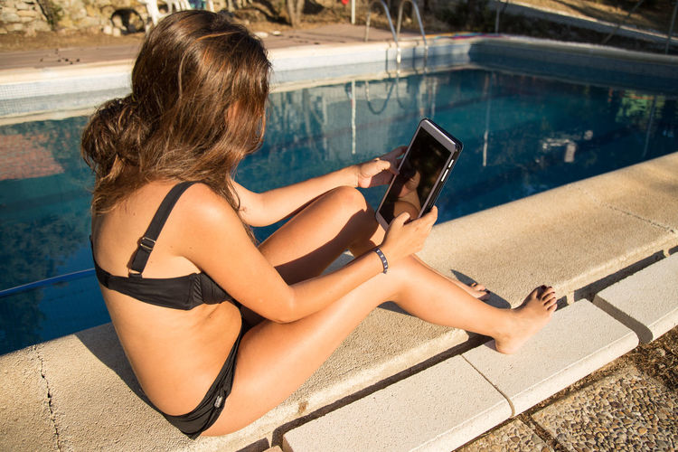 Woman using digital tablet while sitting at poolside during sunny day