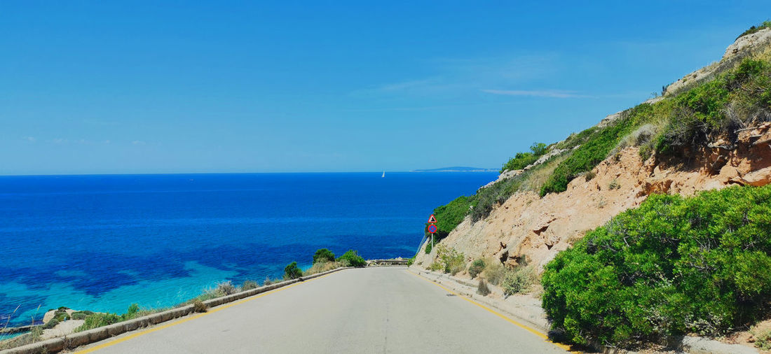 Scenic view of road by sea against blue sky