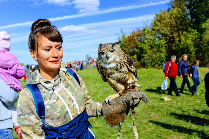 Young woman with eagle owl against sky