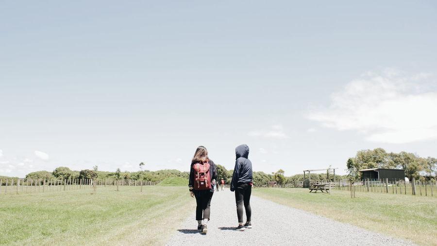 Rear view of women walking on road against sky
