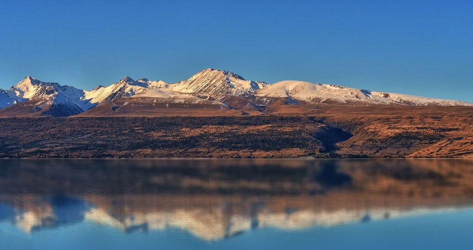 Snow capped mountain range and reflection in Lake Pukaki, NZ Beauty In Nature Blue Day Lake Landscape Nature No People Outdoors Scenics Sky Snow Sunset Travel Water Winter
