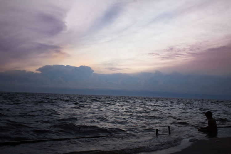 Children were sitting on the beach At sunset Beauty In Nature Calm Cloud Cloud - Sky Cloudy Horizon Over Water Idyllic Leisure Activity Lifestyles Nature Non-urban Scene Ocean Outdoors Remote Rippled Scenics Sea Seascape Shore Sky Sunset Tranquil Scene Tranquility Vacations Water