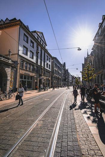 People walking on railroad tracks in city against sky