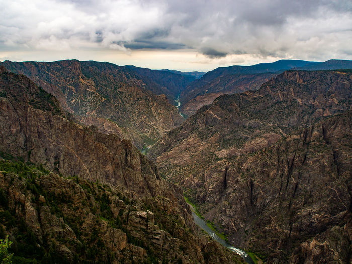 A view of Black Canyon of the Gunnison National Park. Black Canyon Of The Gunnison National Park Nature Scenic Beauty In Nature Canyon Cloud - Sky Day Environment Eroded Geology Idyllic Landscape Mountain Mountain Peak Mountain Range Nature No People Non-urban Scene Outdoors Remote Rock Scenics - Nature Tranquil Scene Tranquility