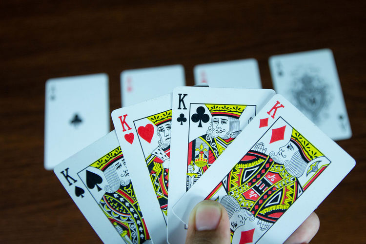Arts Culture And Entertainment Cards Close-up Finger Focus On Foreground Gambling Hand Holding Human Hand Indoors  Leisure Activity Leisure Games Luck One Person Opportunity Playing Poker - Card Game Relaxation Table Text Wood - Material
