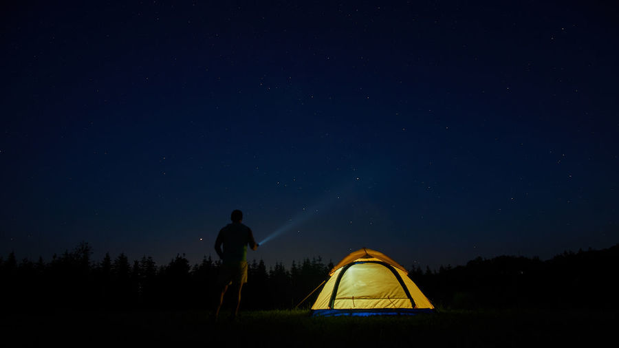 Astronomy Beauty In Nature Camping Field Land Leisure Activity Lifestyles Men Nature Night Outdoors People Real People Scenics - Nature Sky Space Standing Star Star - Space Star Field Tent