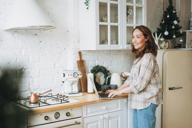 Attractive smiling woman with curly hair in plaid shirt with laptop near window at bright kitchen