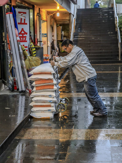 Rice delivery to a local shop in Nanjing, China Real People One Person Architecture Building Exterior Wet Full Length Men Built Structure Water City Lifestyles Street Casual Clothing Rain Rainy Season Incidental People Monsoon Outdoors Nanjing Rice Sacks