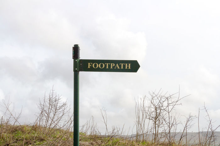 Footpath sign Cloud - Sky Communication Day Footpath Sign Grass No People Outdoors Recreation  Sign Sky Storm Cloud Text