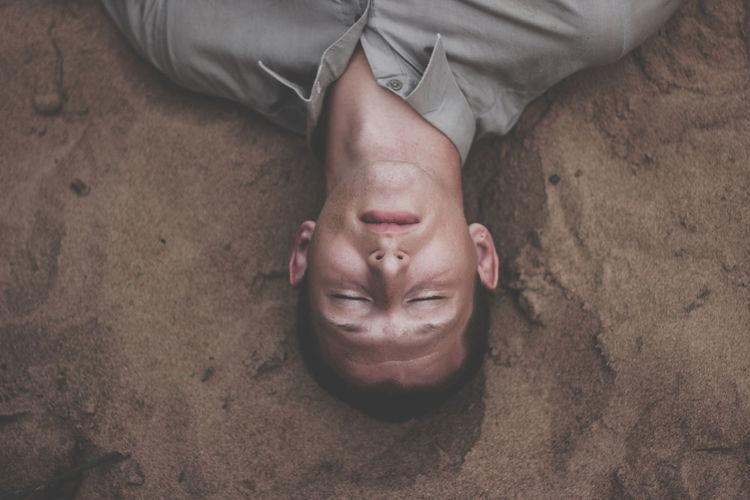 High Angle View Of Man Sleeping On Sand