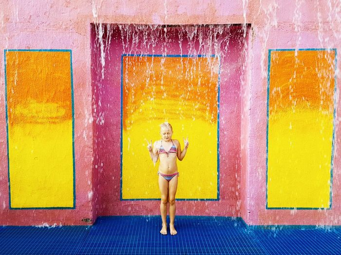 Water Falling On Girl Against Wall