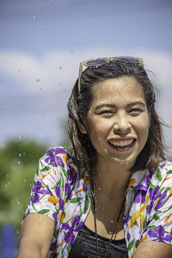 Portrait of smiling woman splashing water against sky
