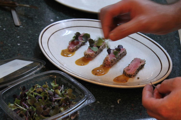 Cropped Hand Preparing Food In Plate On Table