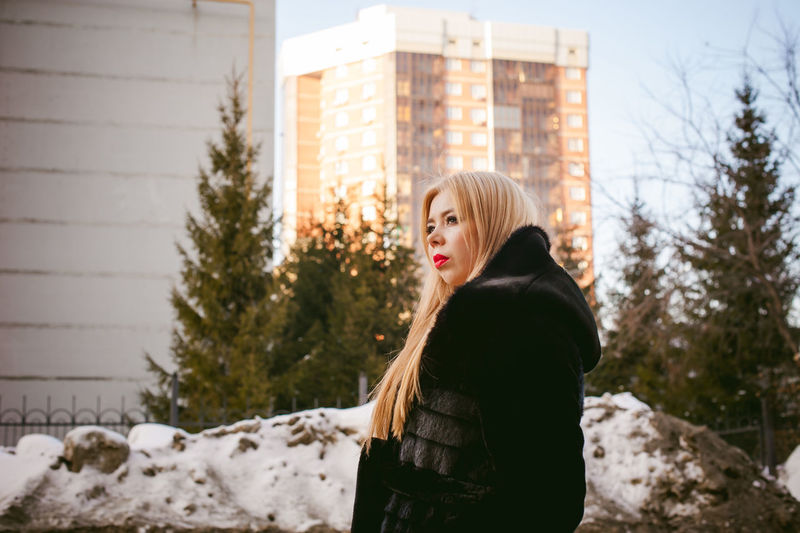 Thoughtful woman in warm clothing against buildings