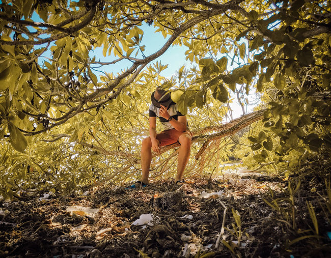 Man Sitting On Branch In Forest