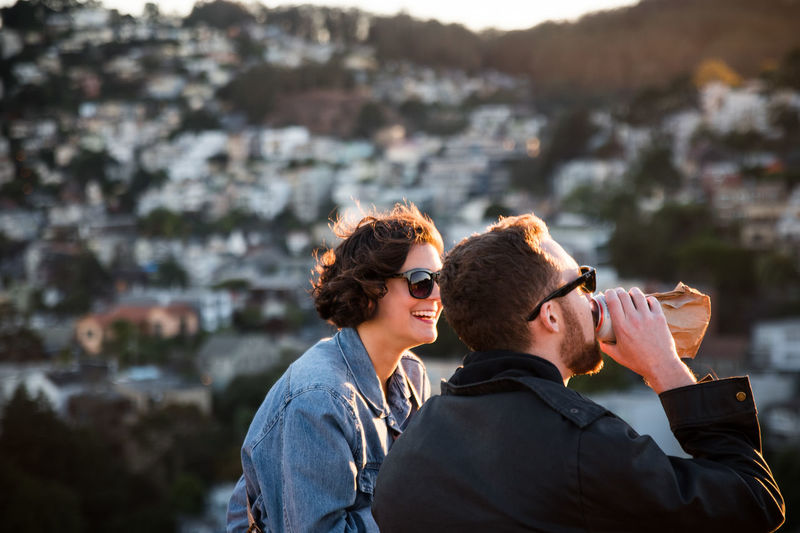 a couple enjoying beer on top of a mountain Beer Casual Clothing Corona Heights Couple Drinking Beer Enjoyment Focus On Foreground Friendship Golden Hour Happy Lifestyles Memories Mountain San Francisco Sunglasses Togetherness Travel Destinations Twin Peaks Young Adult People And Places