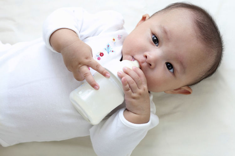 chinese baby Asian  Baby Care Innocence Adorable Child Childhood Chinese Cute Drinking Milk Facial Expression Healthy Infant Kid Lifestyles Little Looking At Camera Lying Down Milk Bottle One Person Portrait Real People Toddler  White Young