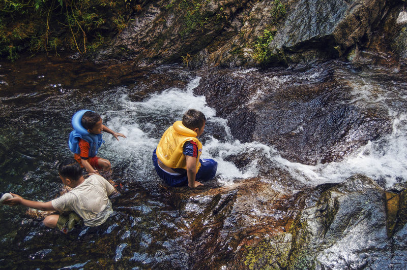 People enjoying by waterfall at forest