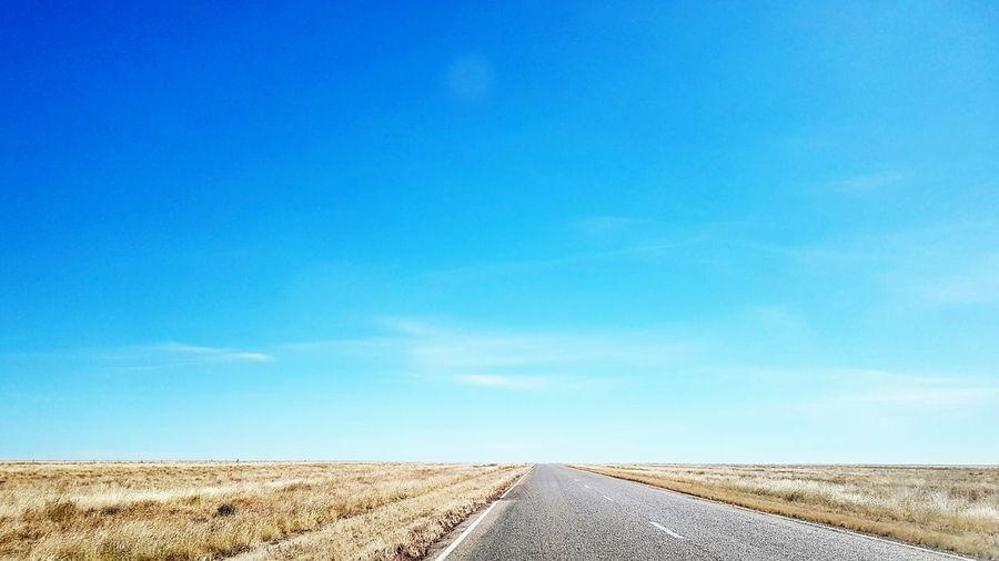 Road leading towards blue sky