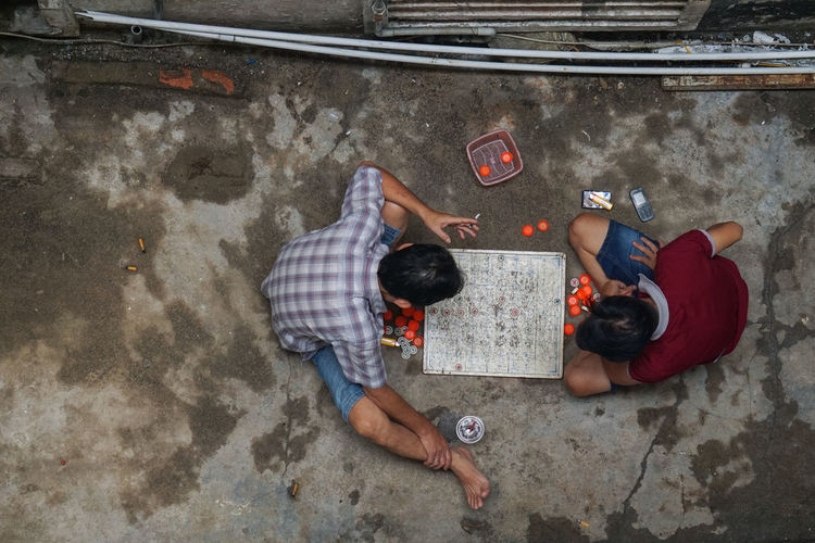 High angle view of friends lying on floor in city