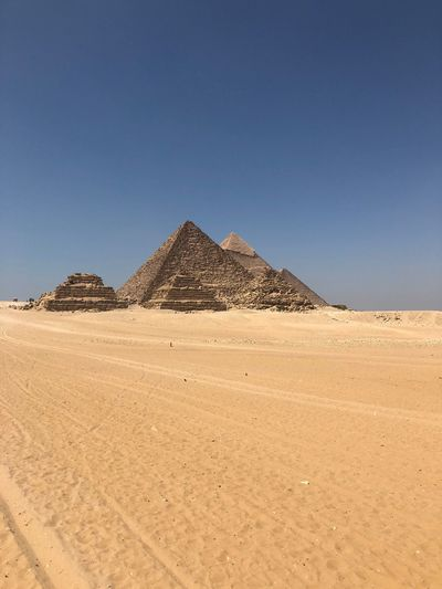 Pyramids at desert against clear sky