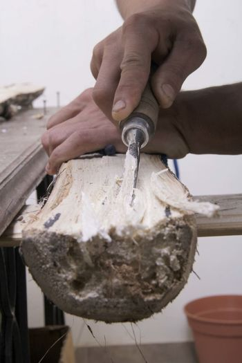 Close-up of craftsperson using tool on wood at workshop