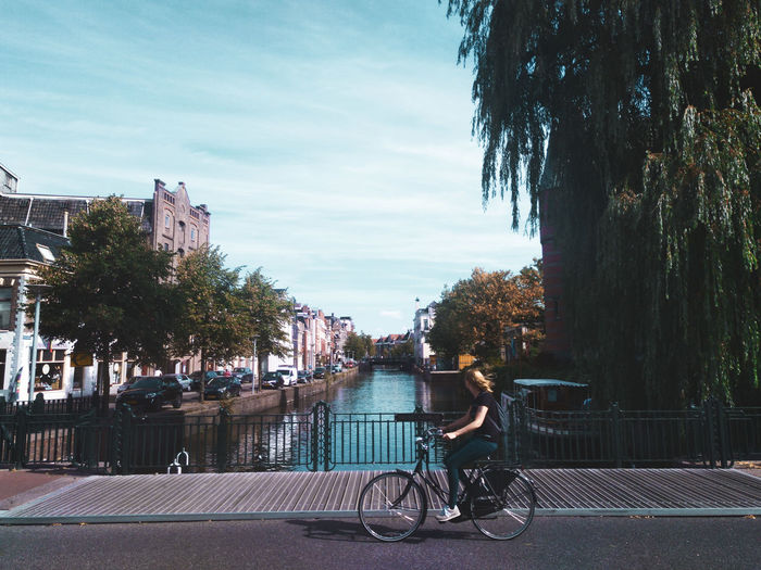 She just passed by.. Bycicle Passing By Tree City Water Full Length Sky Architecture Footbridge Sidewalk