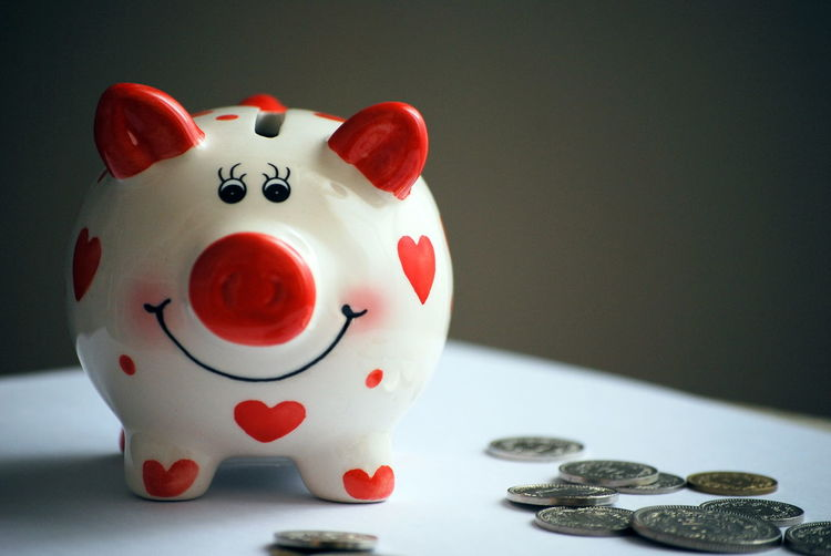 Close-Up Of Coins With Piggy Bank On Table Against Wall