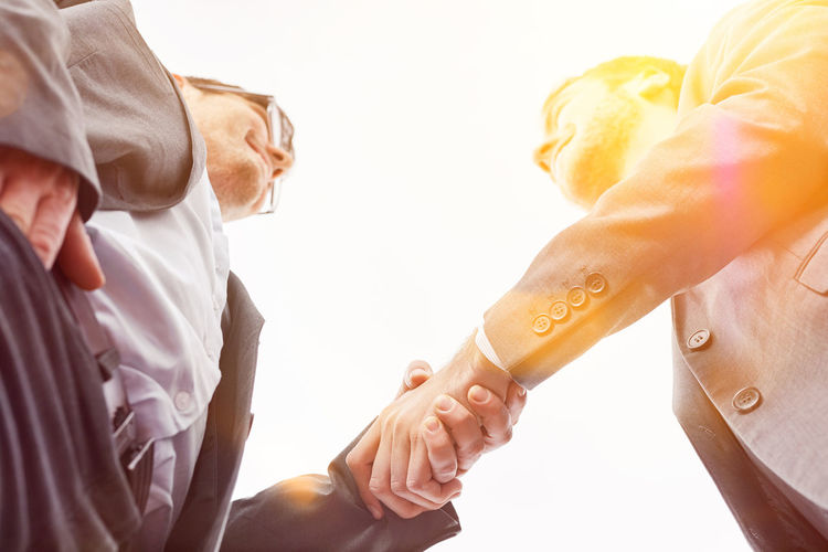 Directly below shot of business persons shaking hand against sky