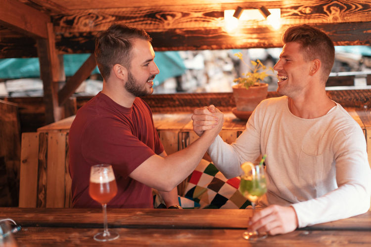 Two friends sitting at the bar strike a deal clenching hands and smiling