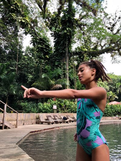 Girl gesturing whole standing by swimming pool