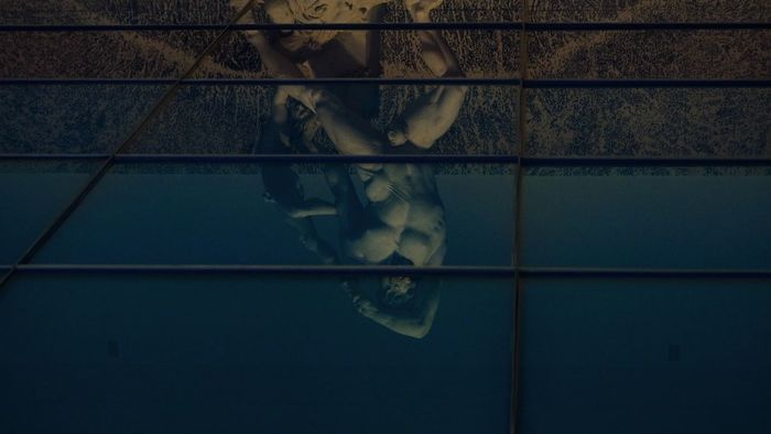 LOW SECTION OF PERSON WITH REFLECTION ON WATER IN GLASS