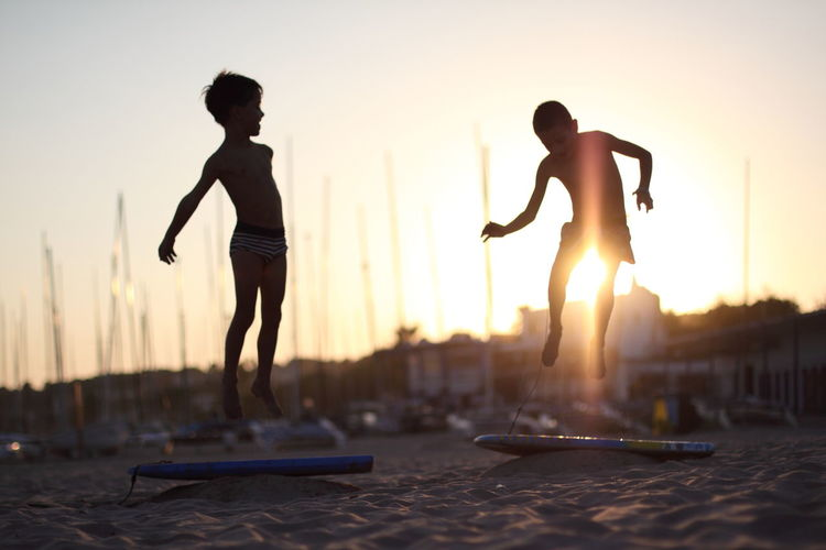 Silhouette men with arms raised against sky during sunset