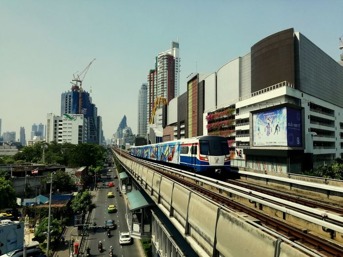 Train on road in city against sky